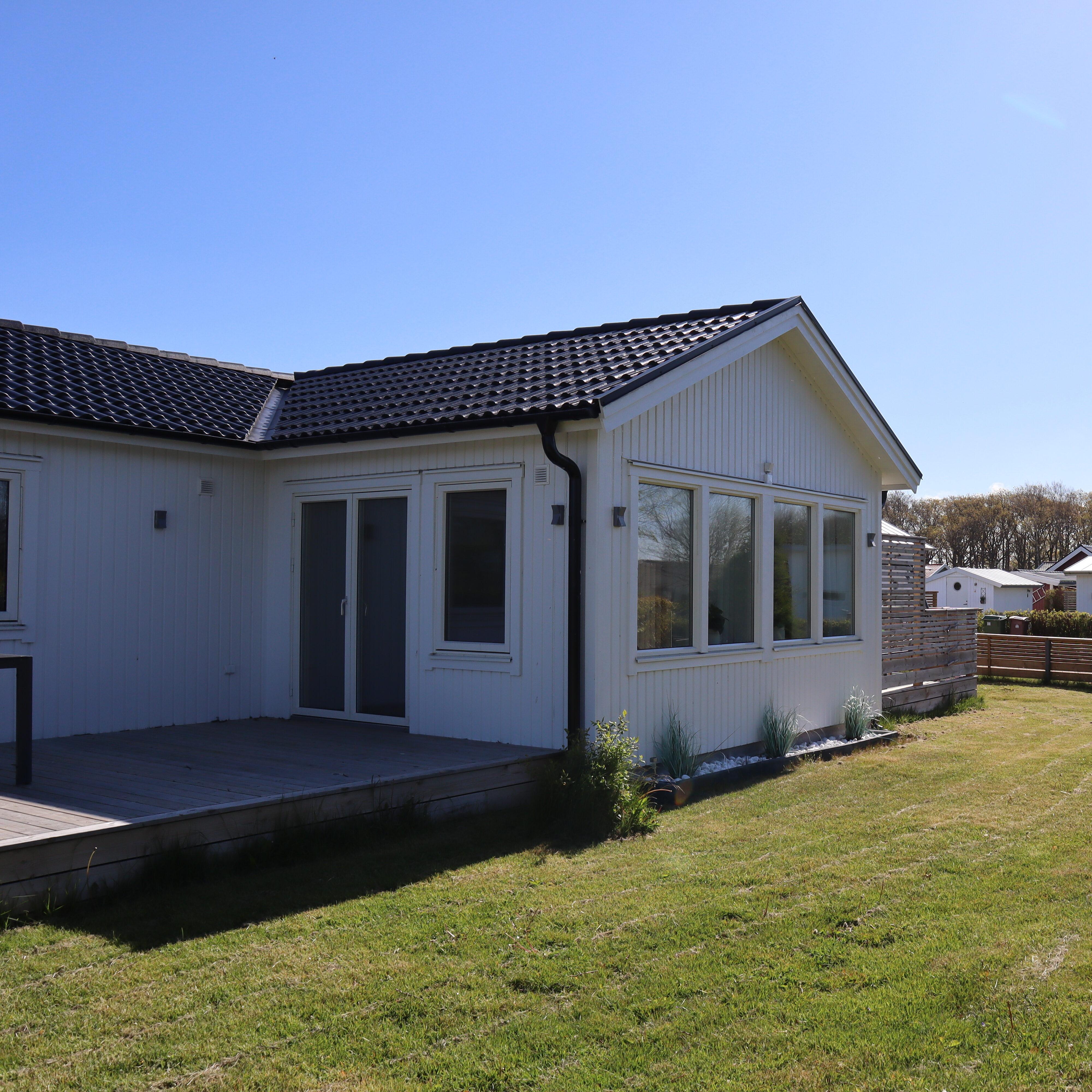 Nybyggt hus med vit fasad och nya fönster