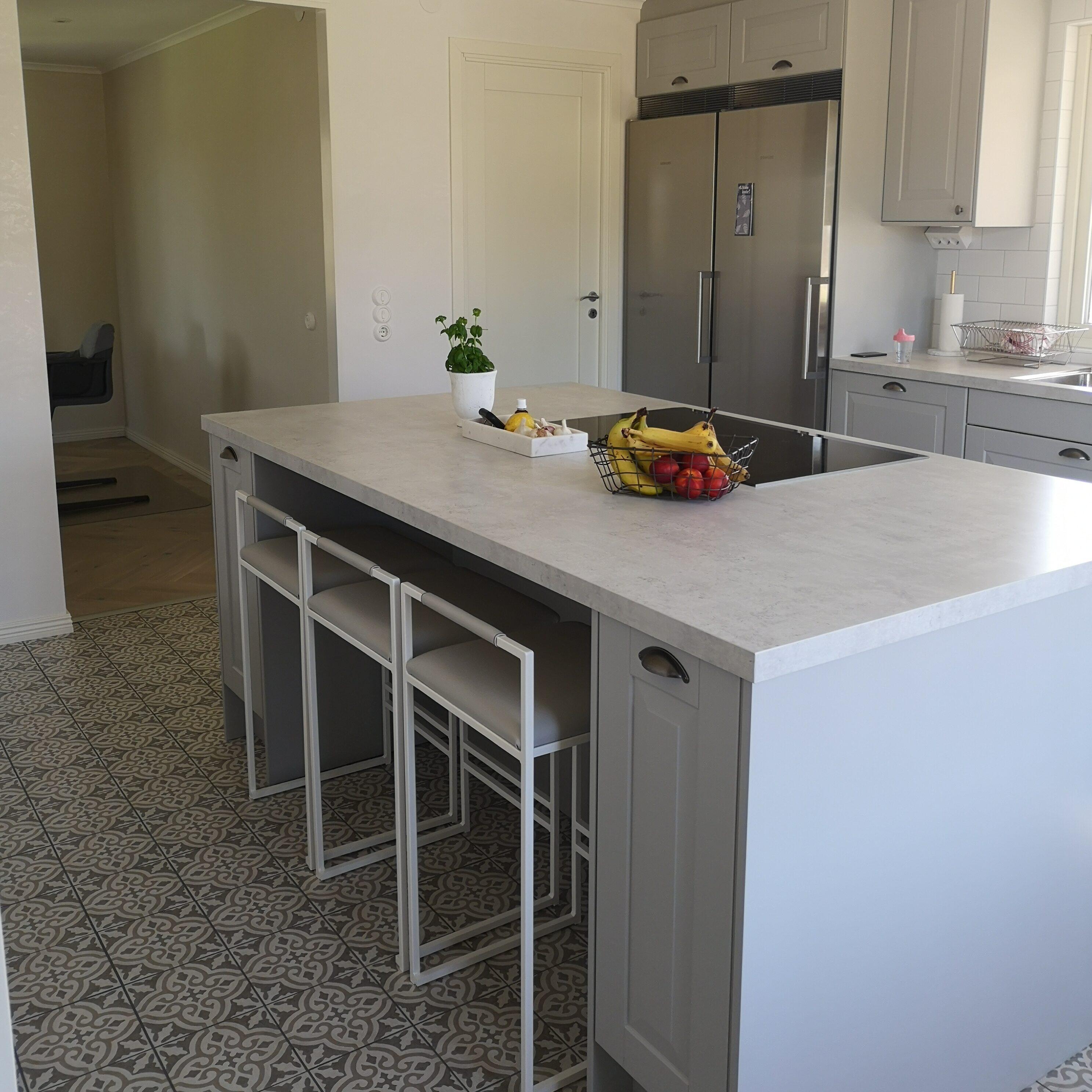 Ljusgrått kök med köksö och marockanskt golv