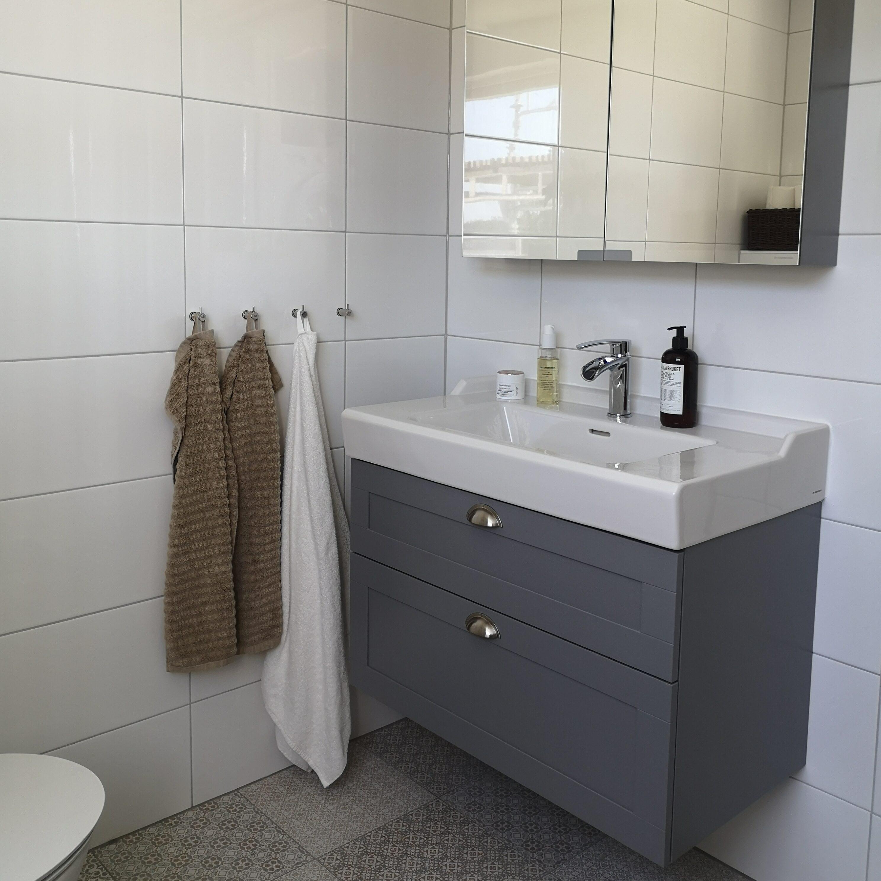 Ljust badrum med grå kommod